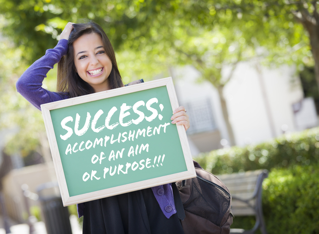 Excited Mixed Race Female Student Holding Chalkboard With Success and the Definition Written on it.